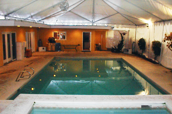 frame tent installed over a pool for an annual december pool party in seattle